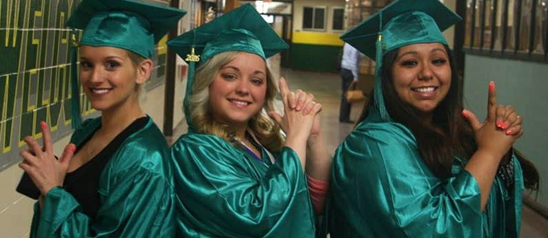 Three First Institute Graduates in full cap and gown in a Charlie's Angels pose.