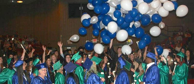 A graduating class at the graduation ceremony. Everyone is is cap and gown and white and blue balloons are falling from the ceiling.