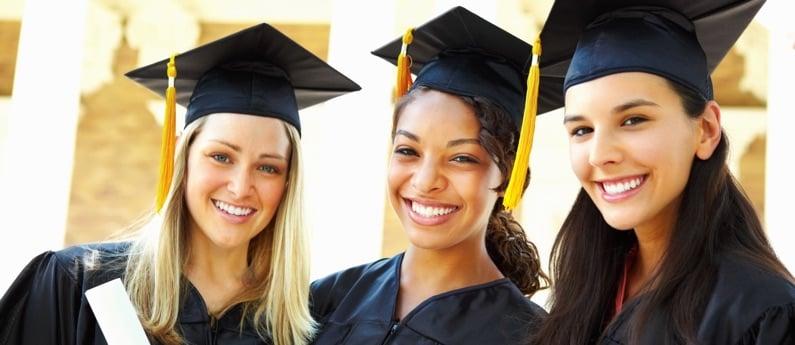 Three First Institute Graduates in full cap and gown.