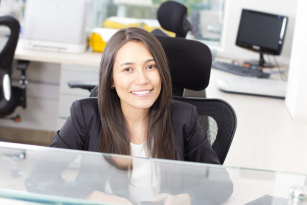 Attractive, smiling female medical assistant sitting behind a counter