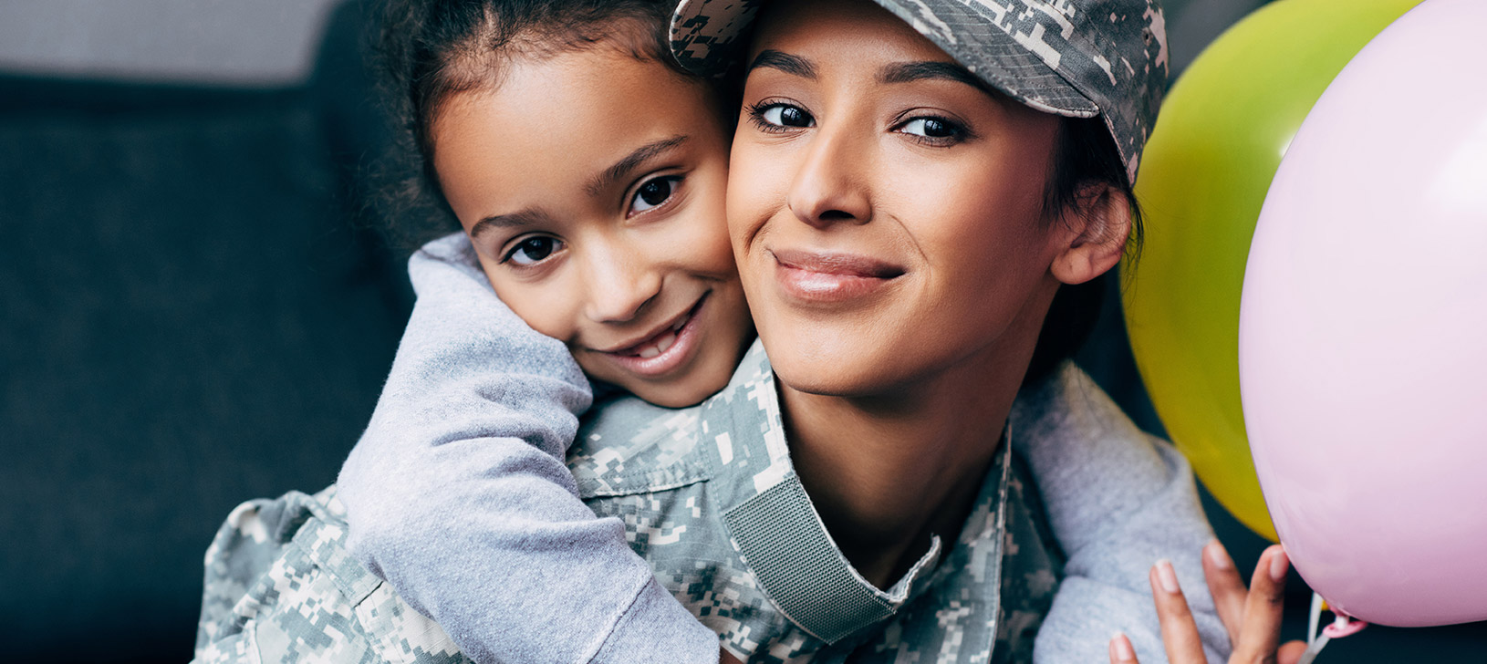 Close up of smiling military family of three. The father is holding their son. They are standing in front of an American flag.